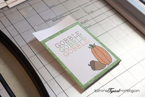 """A Thanksgiving utensil holder with """"gobble, gobble, gobble"""" written on front."""