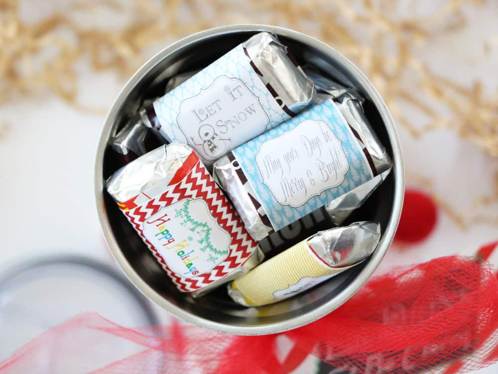 birds eye view of a tumbler filled with mini candy bars on a white counter next to red ribbon and brown crinkle paper