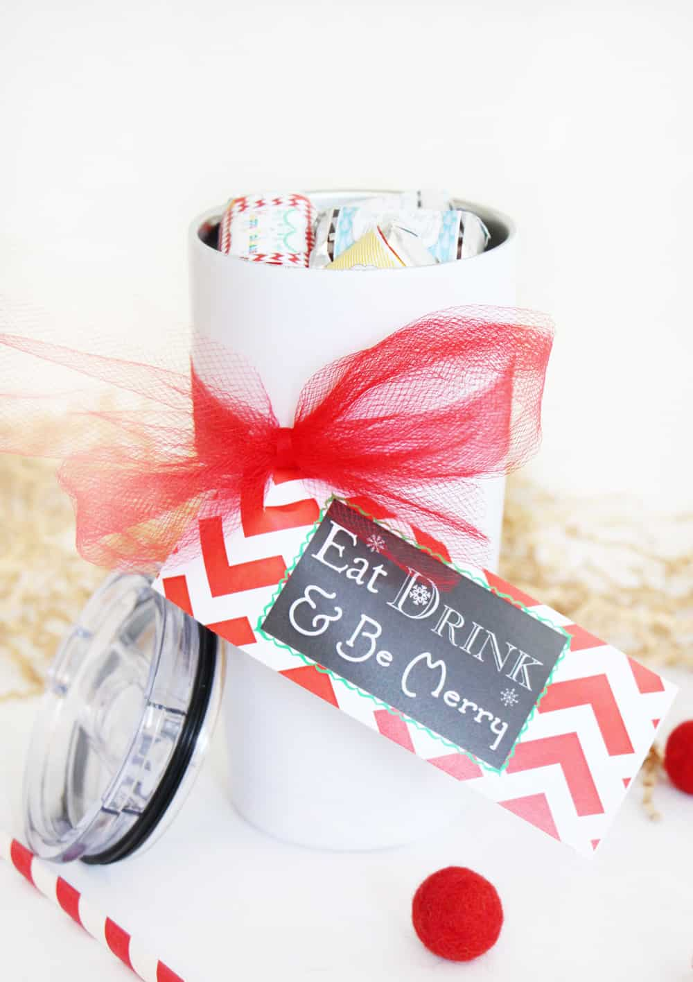white tumbler with Christmas tag and red ribbon against a white background