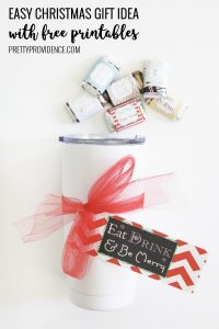 white tumbler with christmas tag on white counter with mini candy bars above it