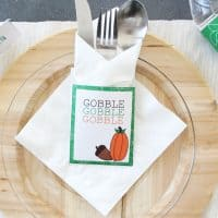 Free Thanksgiving Printable utensil holder, white card stock with a green border with words 'Gobble, Gobble, Gobble' on it.