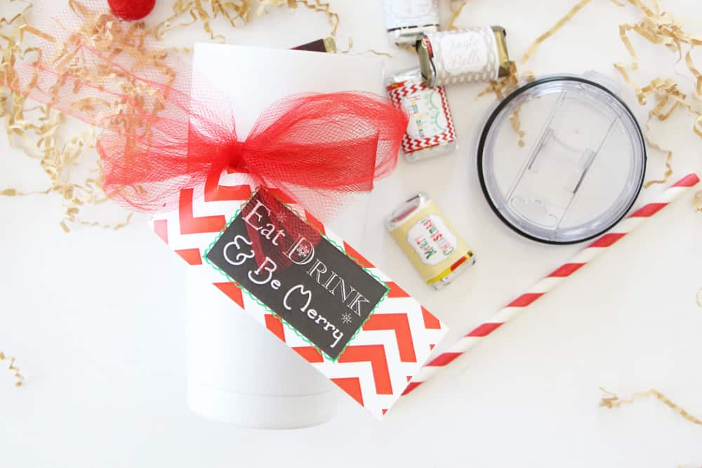white tumbler with christmas tag on white counter with red and white straw, candy bars and brown crinkle papers