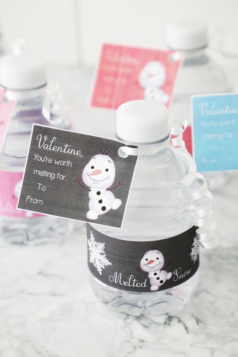 mini water bottle with frozen valentine wrapper on a granite counter