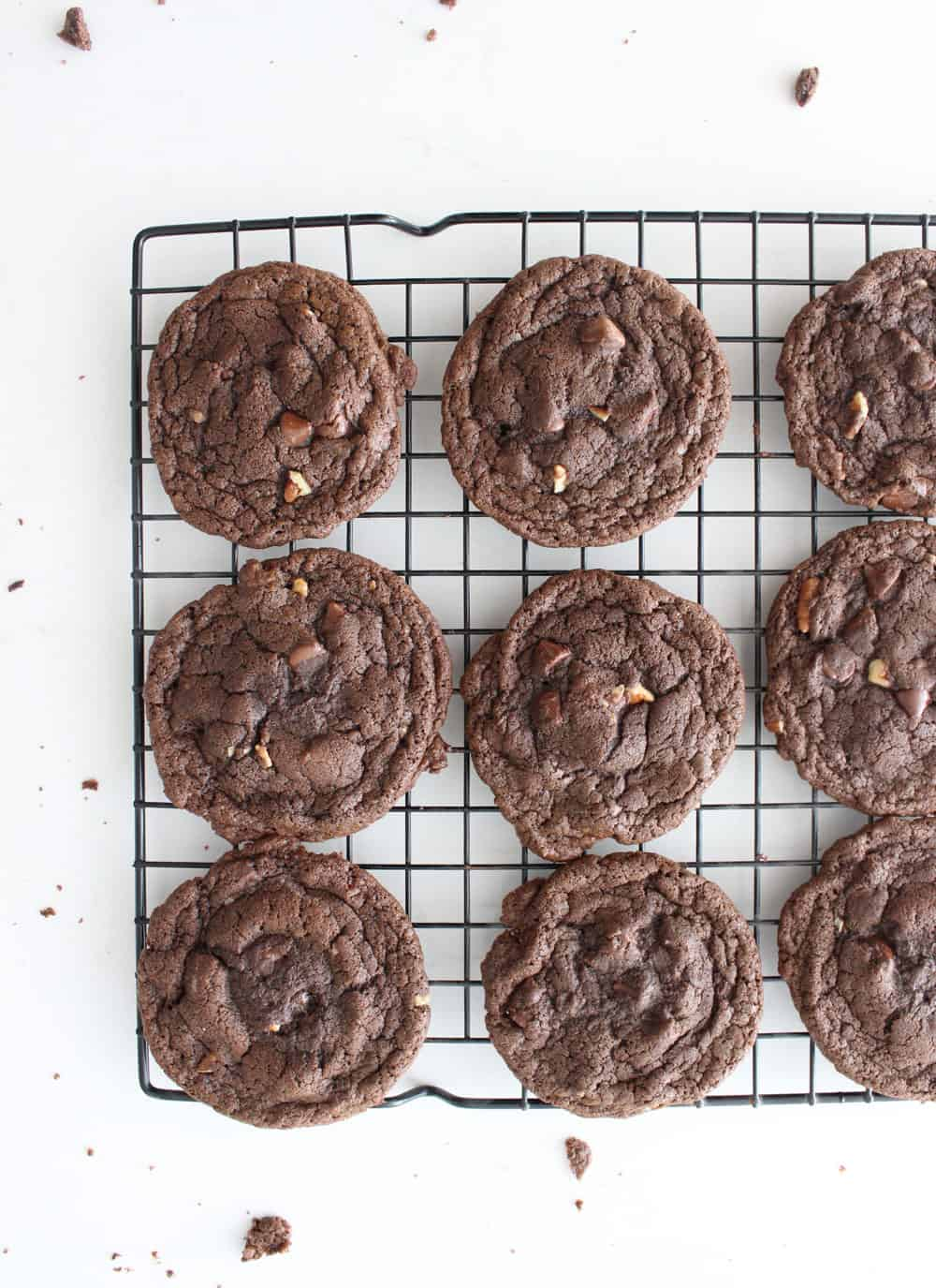 Double chocolate chip cookies lined up on a cooling rack on a white countertop