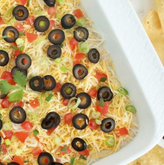 Seven layer bean dip in a white dish with chips