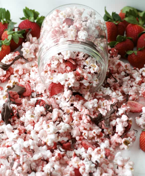 Chocolate Covered Strawberry Popcorn - Pink popcorn with freeze-dried strawberries and dark chocolate drizzled on top, spilling out of a glass jar with strawberries in the background.