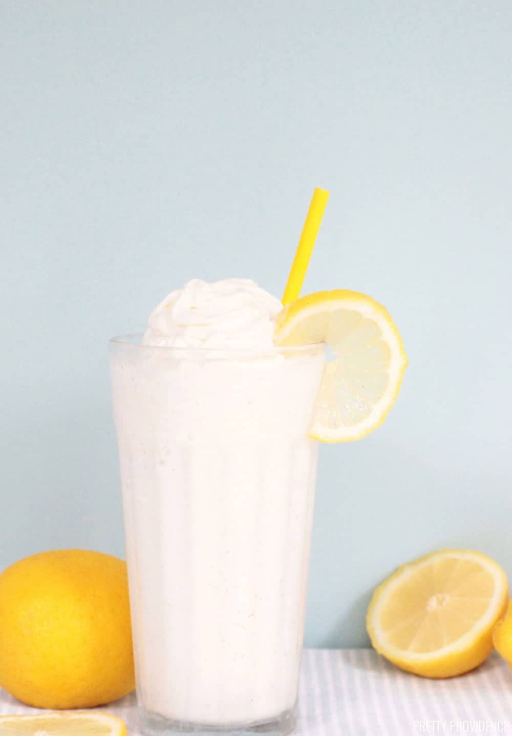 Frosted Lemonade or Frozen Lemonade in a glass with whipped cream on top, a yellow straw and lemon slice on the side.