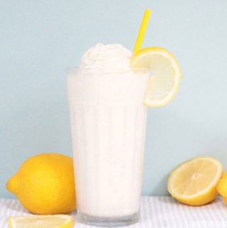 Frosted Lemonade in a glass topped with whipped cream and a lemon slice and surrounded by fresh lemons.