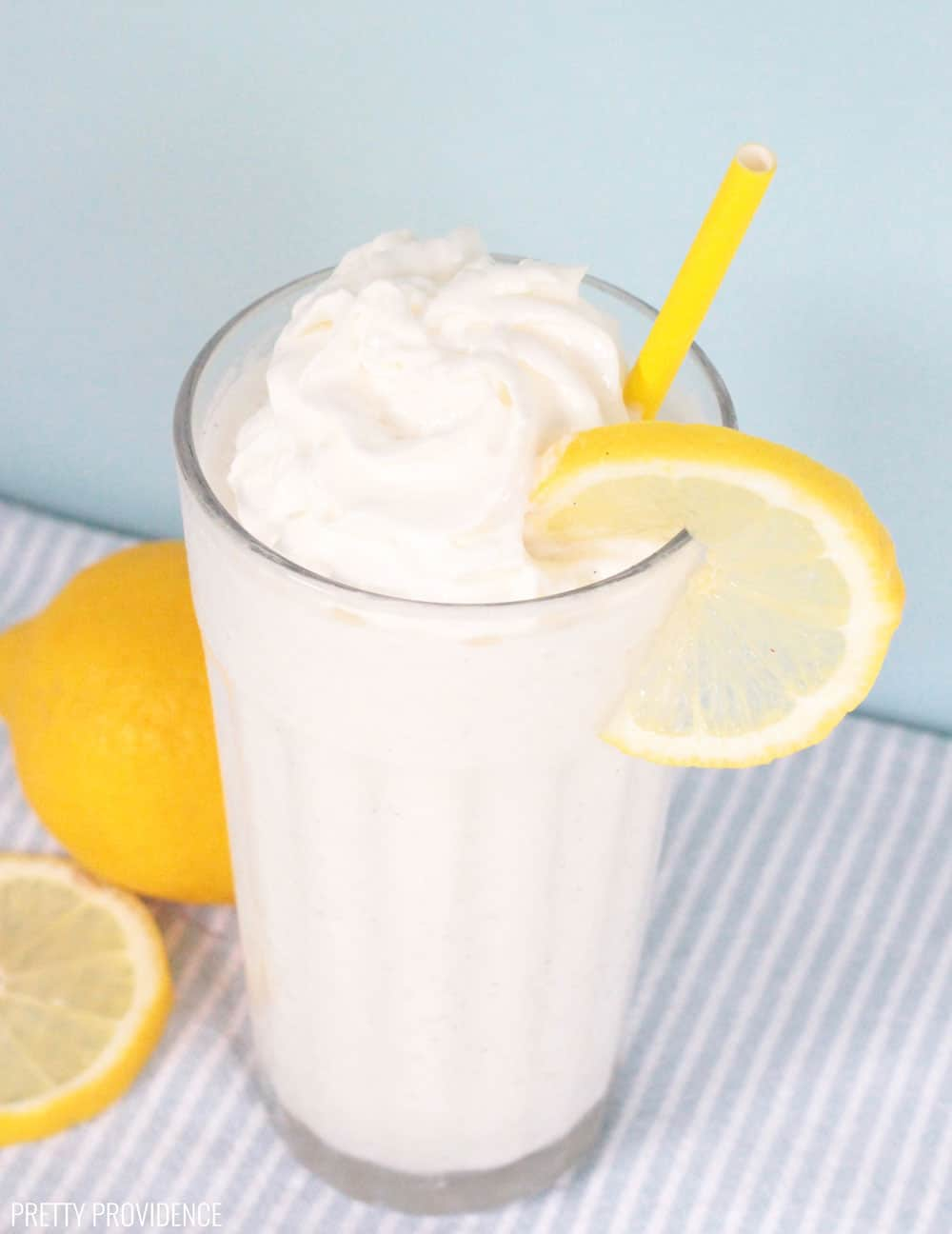 Frozen lemonade in a clear glass with ice cream, whipped cream on top, and garnished with a lemon slice and yellow straw.