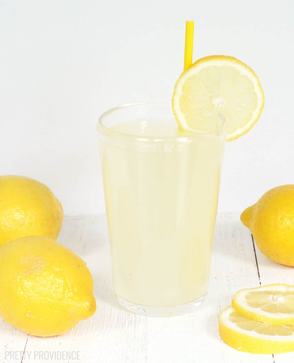 Fresh squeezed lemonade in a clear glass with lemon slice and yellow straw as garnish and lemons around it on the sides.