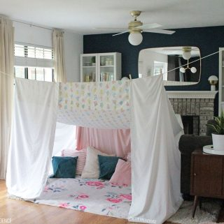 Canopy style blanket fort in a living room made with bedsheets, clothes pins, and clothesline tied from door hinge to door hinge. Inside the fort are pink, blue and cream colored pillows.