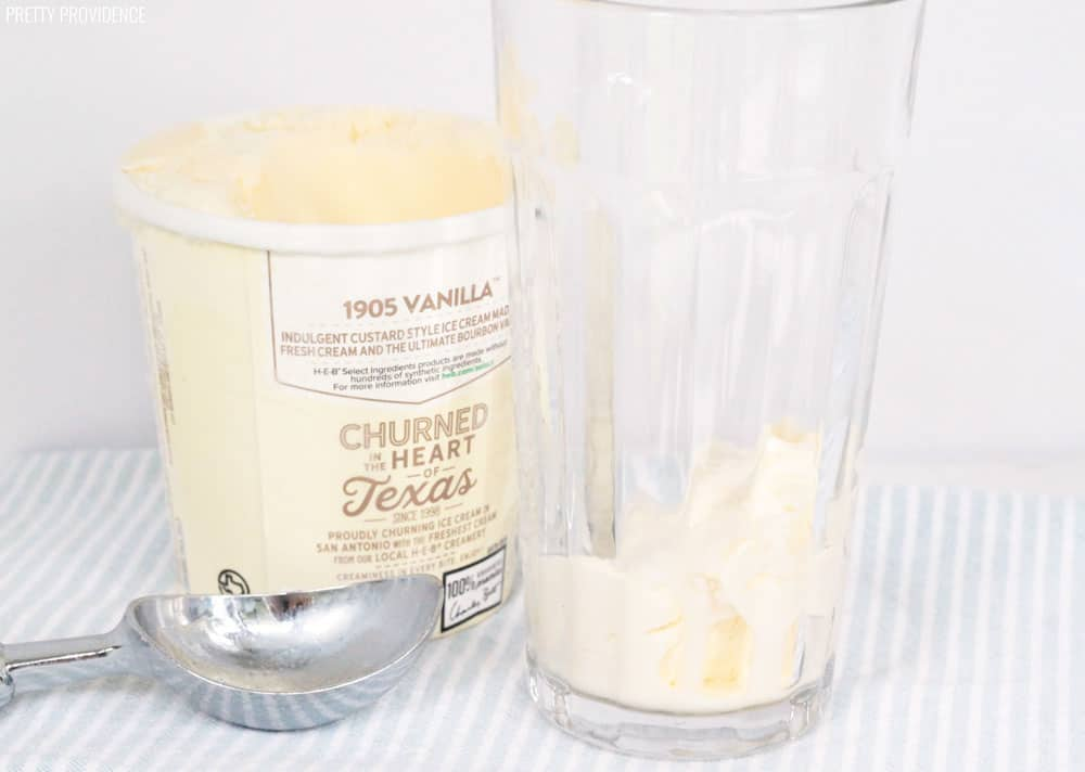 Pint container of vanilla ice cream, a silver ice cream scoop and a scoop of vanilla ice cream in the bottom of a tall glass.