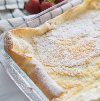 German Pancakes just out of the oven, dusted with powdered sugar in a glass baking dish.
