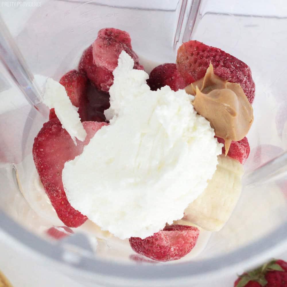 Strawberry Banana Protein smoothie ingredients in a blender. Yogurt, peanut butter, frozen strawberries, milk and banana.