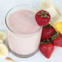 Strawberry banana protein smoothie in a glass with strawberries, a peeled banana and sliced banana surrounding the glass.