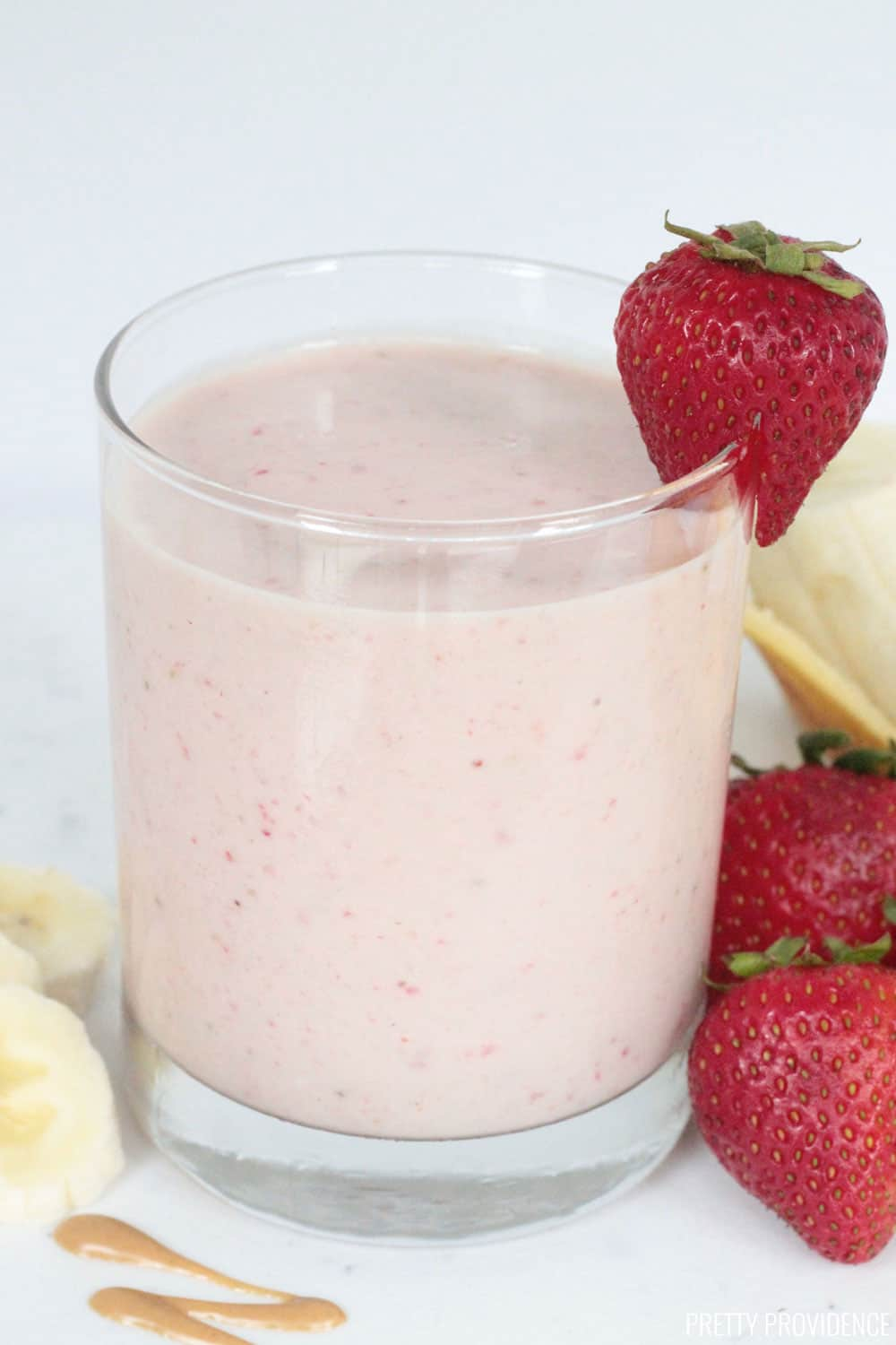 Strawberry banana protein smoothie with strawberries on the side and banana slices.
