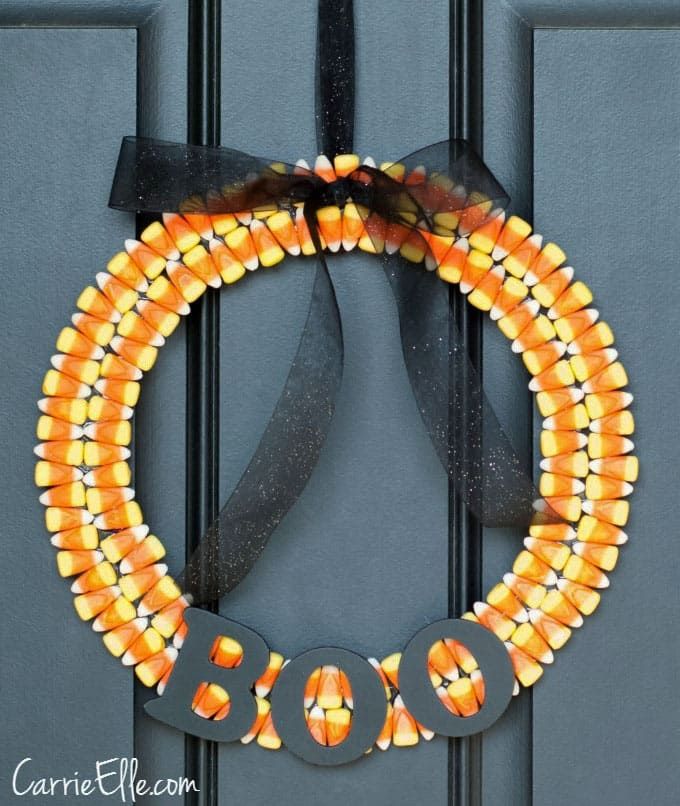 Candy corn wreath on a black front door.