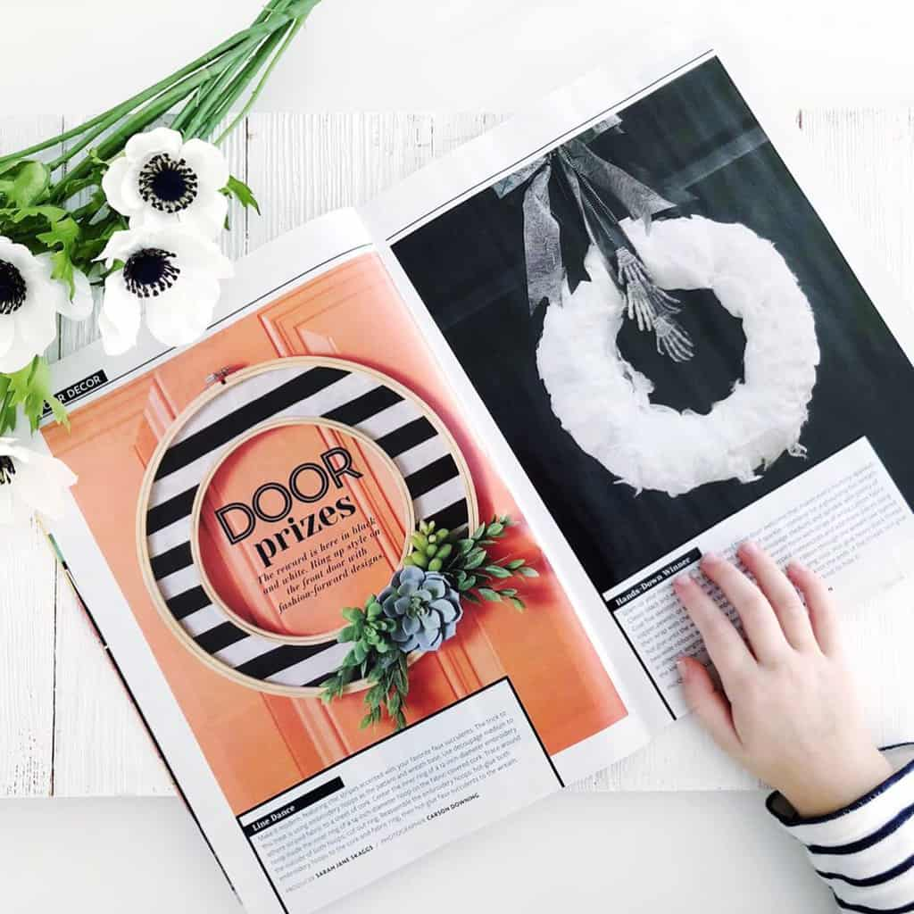 Black and White Striped Hoop Wreath in a Magazine next to a white Halloween wreath.