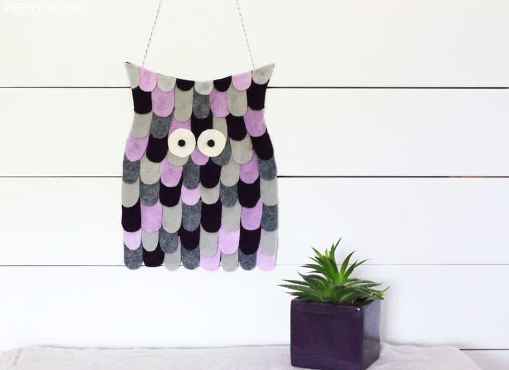 Felt owl Halloween decoration on a white wall with a succulent plant next to it.