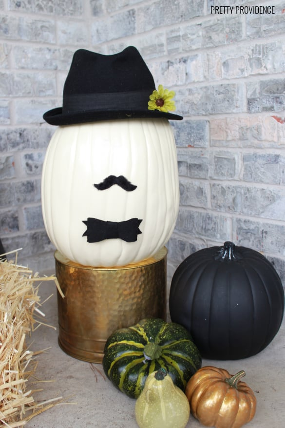 Pumpkin dressed up like a man wearing a hat, mustache and bow-tie on a porch with other pumpkins and gourds.