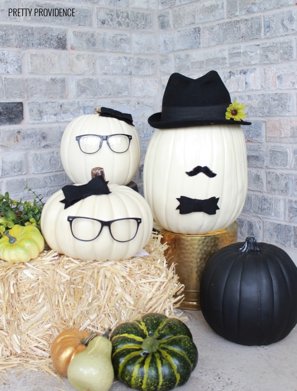 No-Carve Pumpkins wearing glasses, hats, bows and mustaches on a hay bail. Fall porch decoration.