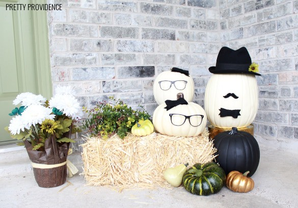 Pumpkin people. No-carve pumpkin idea with craft pumpkins wearing glasses, bows and hats on a porch with a hay bail and fall flowers.