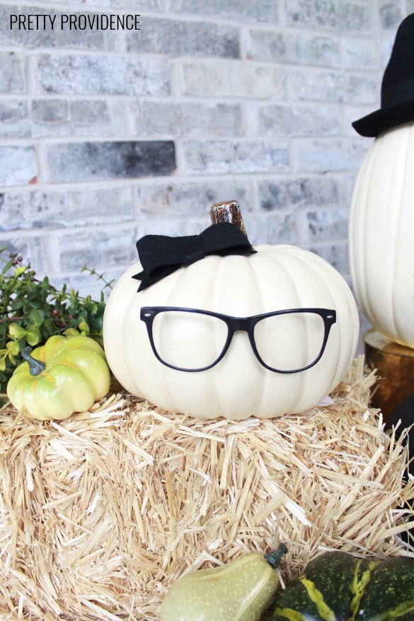 No-carve pumpkin wearing glasses, bows and hats on a porch with a hay bail and fall flowers.