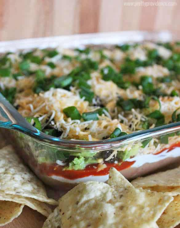 Seven layer dip in a 9x13 glass dish, topped with cheese and sour cream, with tortilla chips on the side.