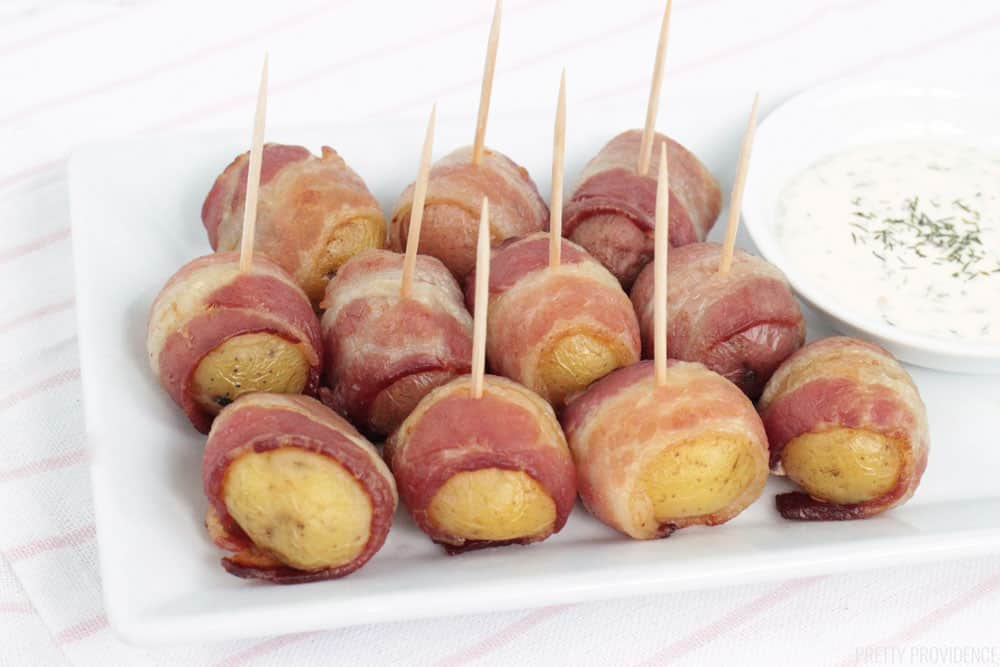 Bacon Wrapped Potatoes with toothpicks on a white plate with creamy dill sauce on the side.