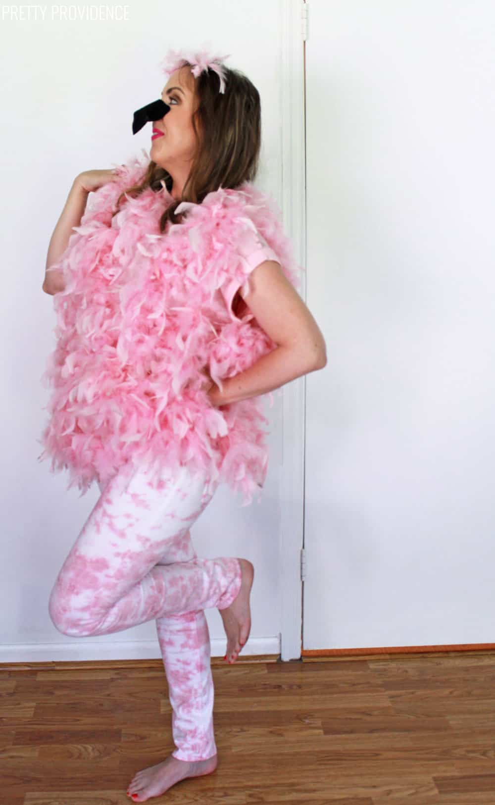Woman in pink flamingo Halloween costume made with pink feather boas, posing like a flamingo on one leg.