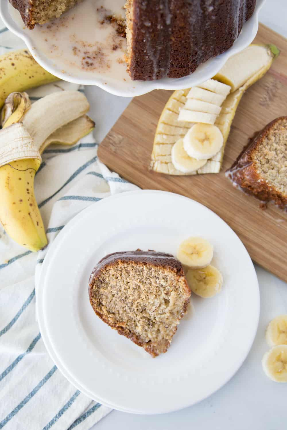 Banana cake on a white plate with bananas sliced as garnish and a beautiful cutting board under it.