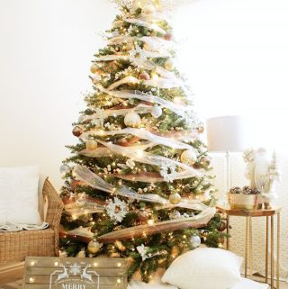 dream christmas tree decorated using bronze, silver, and gold surrounded by pillows and decor