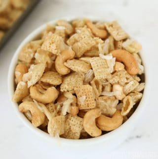Gooey Chex mix - Chex, cashews, coconut, almonds with sticky caramel coating in a white bowl.