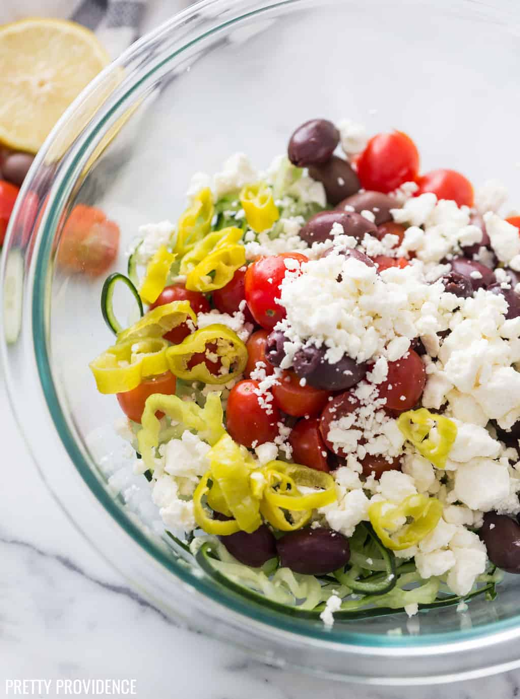 Greek salad ingredients in a bowl with feta cheese, pepperoncini, tomatoes, kalamata olives and spiralized cucumber.