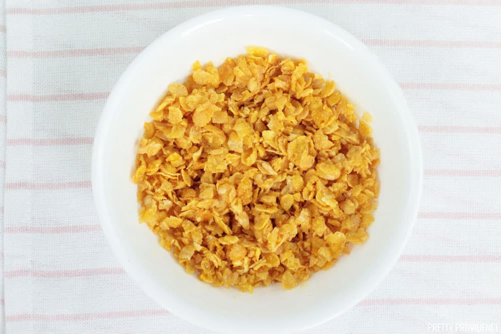 Corn flakes crushed and mixed with melted butter, resting in a white bowl.