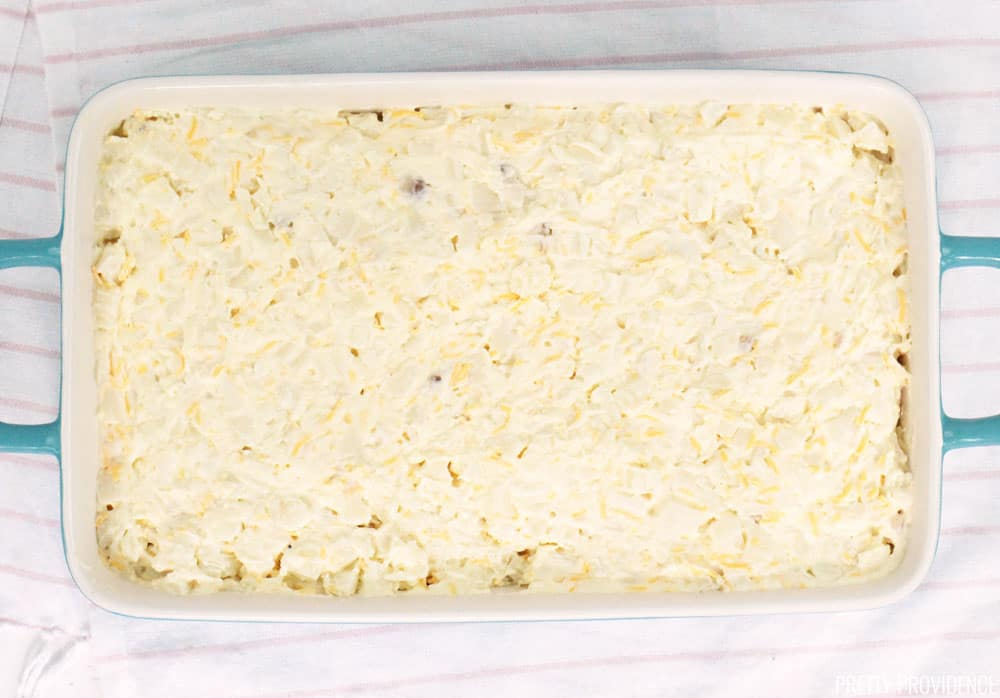 Funeral potatoes casserole uncooked in a 9x13 dish.