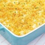 Potato Casserole AKA Funeral Potatoes in a blue 9x13 baking dish topped with cornflakes and chives.