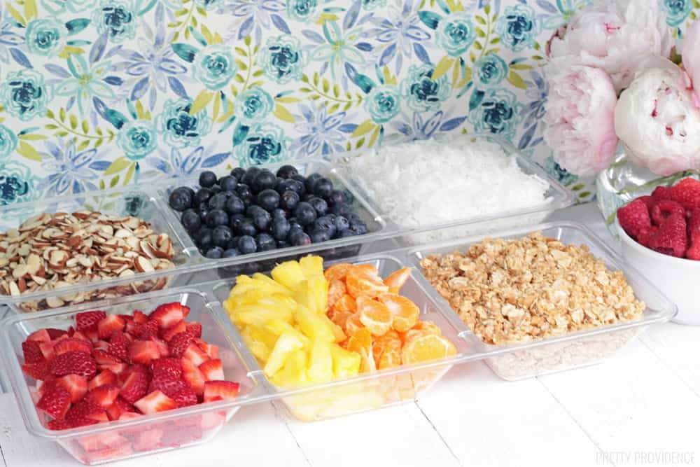 Strawberries, blueberries, raspberries, pineapple, oranges, almonds, coconut and granola yogurt toppings in a clear dish.