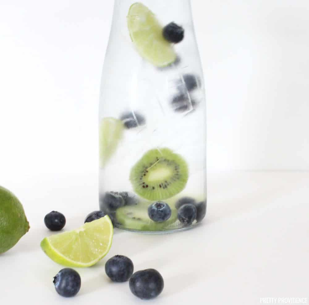 Fruit Infused Water Recipe, blueberry kiwi and lime slices in a glass pitcher of cold water.