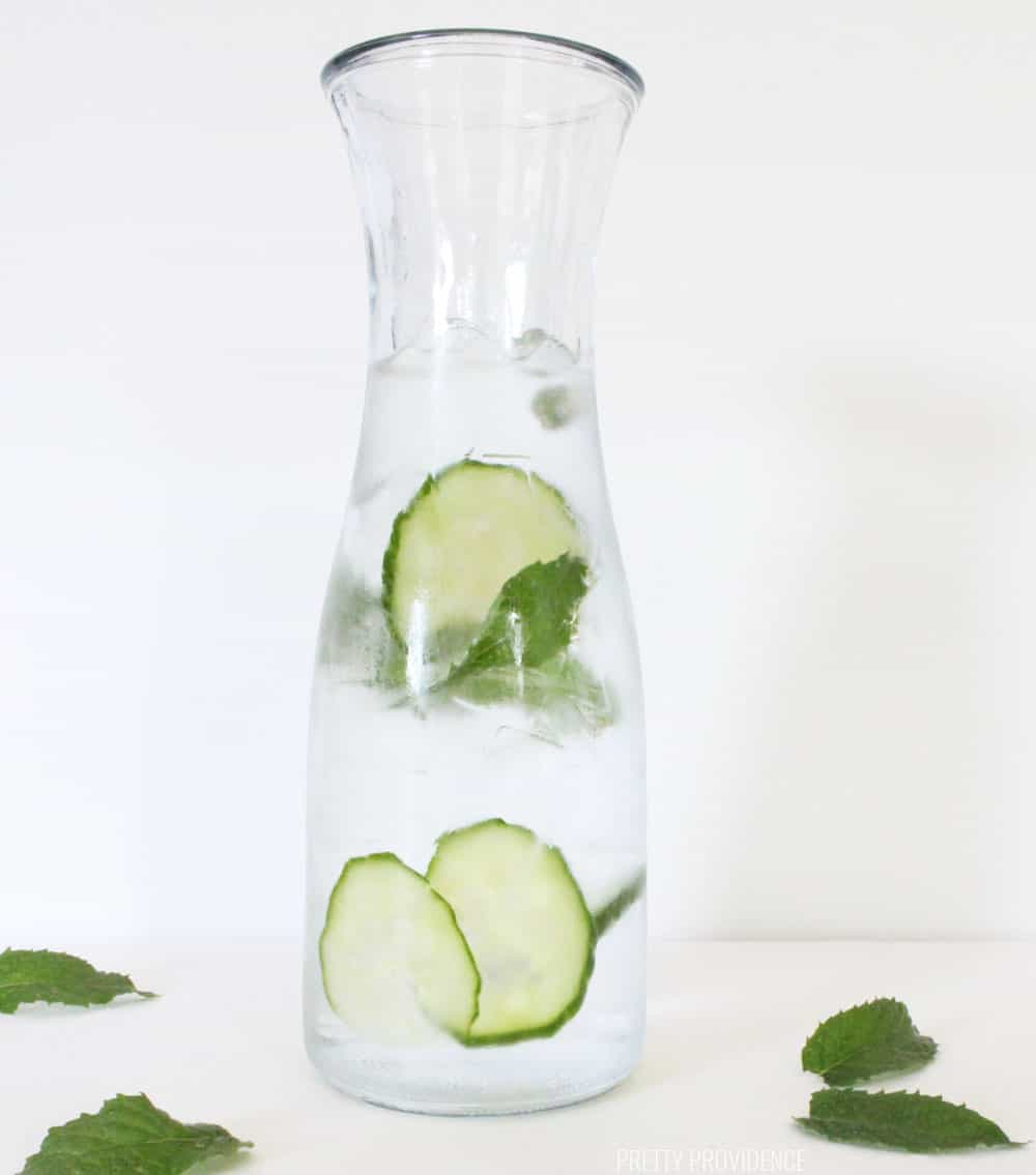 Cucumber slices and mint leaves in cold water, infused water recipes.