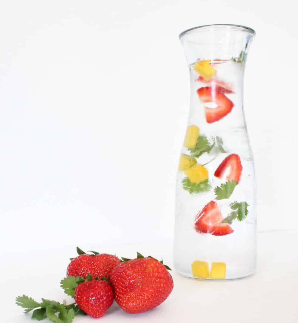 Strawberry slices, mango and cilantro in cold water in a glass pitcher, ruit infused water recipe.