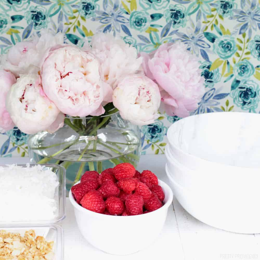 Raspberries in a small white bowl, pink peonies in a clear vase, and bowls for a yogurt bar brunch.
