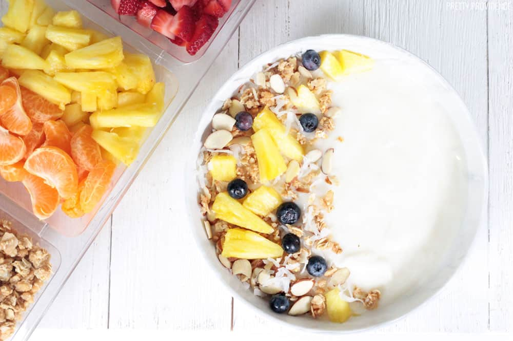 Vanilla yogurt with granola, coconut, pineapple and blueberries in a white bowl.