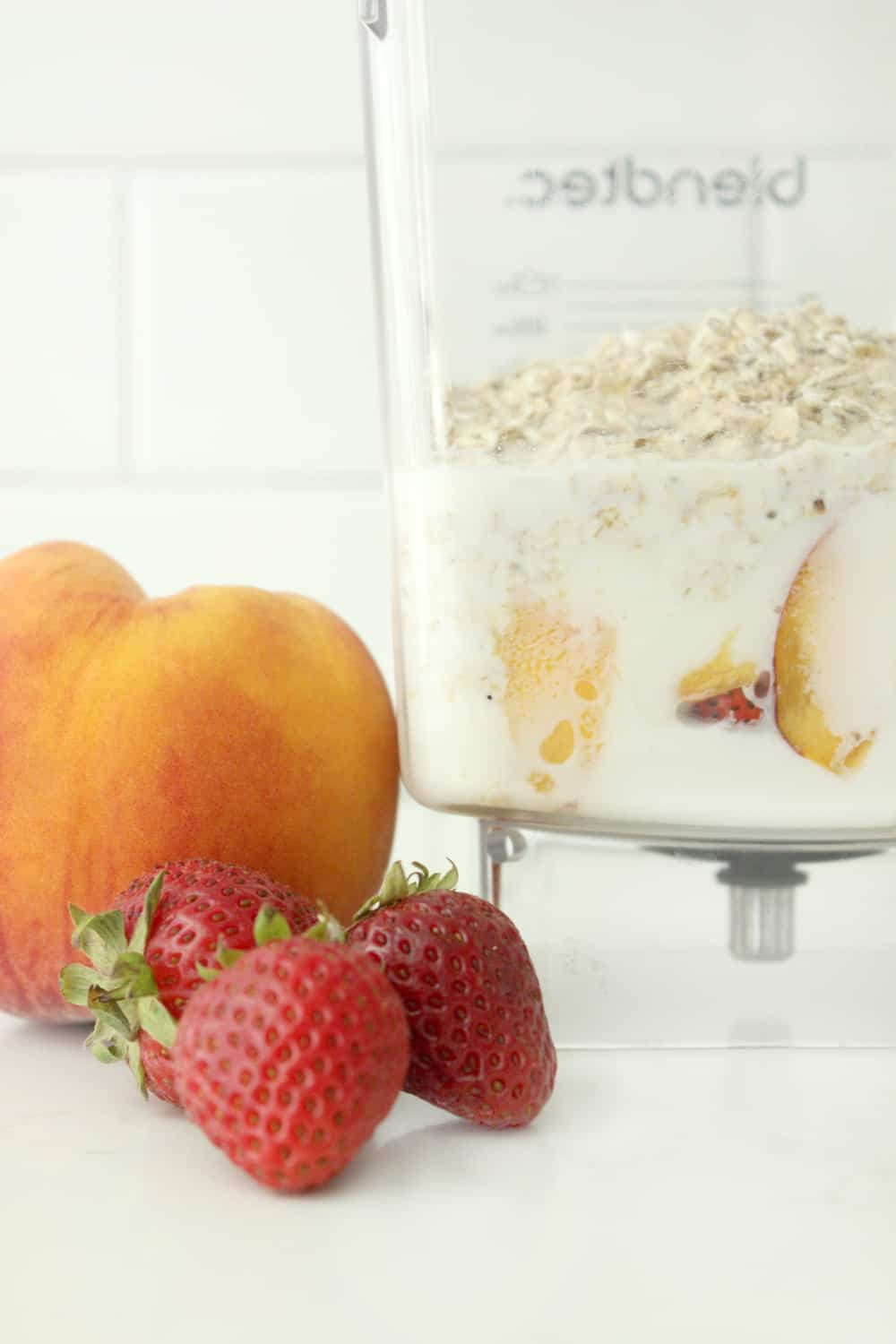 ingredients for a strawberry peach smoothie shown in the blendtec