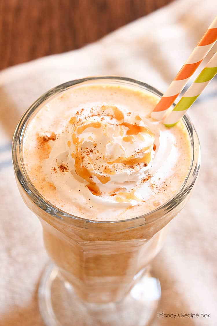 Close up shot of a pumpkin milkshake topped with whipped cream and caramel sauce