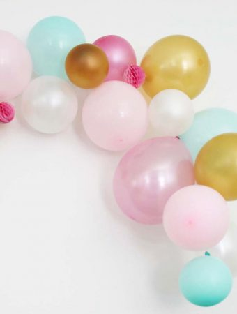 Balloon Garland with Pink, Blue, Gold and White Balloons against a white wall.