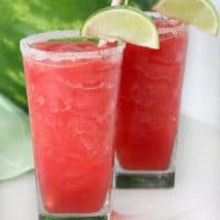 two watermelon slushes in clear glasses in front of a full watermelon