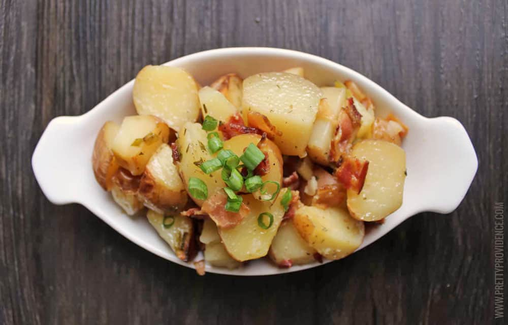 Slow Cooker Ranch Potatoes in a white serving dish topped with green onions and bacon