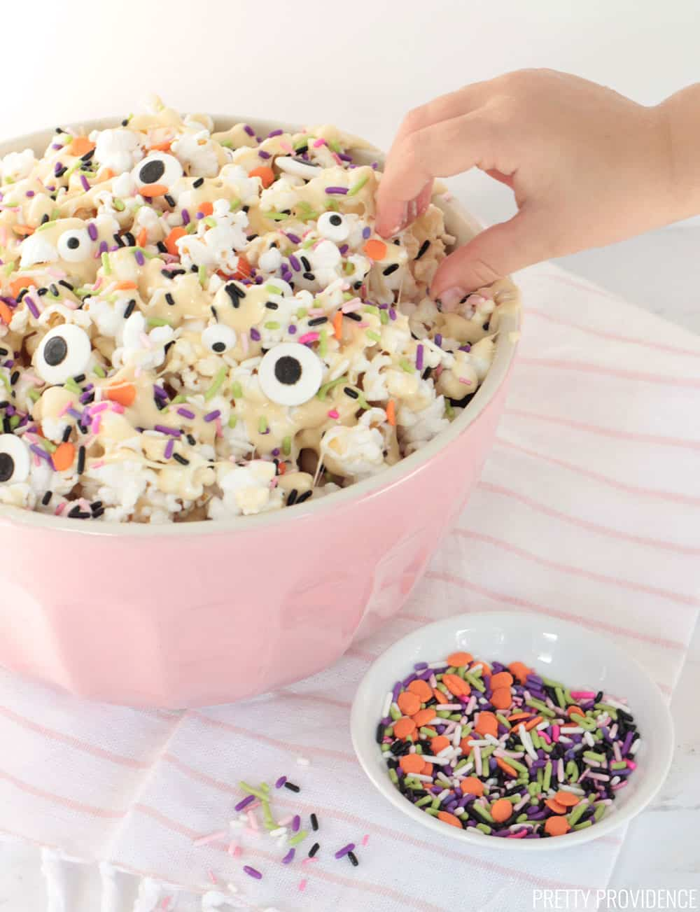 Halloween popcorn in a pink mixing bowl, candy eyeballs and Halloween sprinkles on top, a small hand reaching for popcorn.