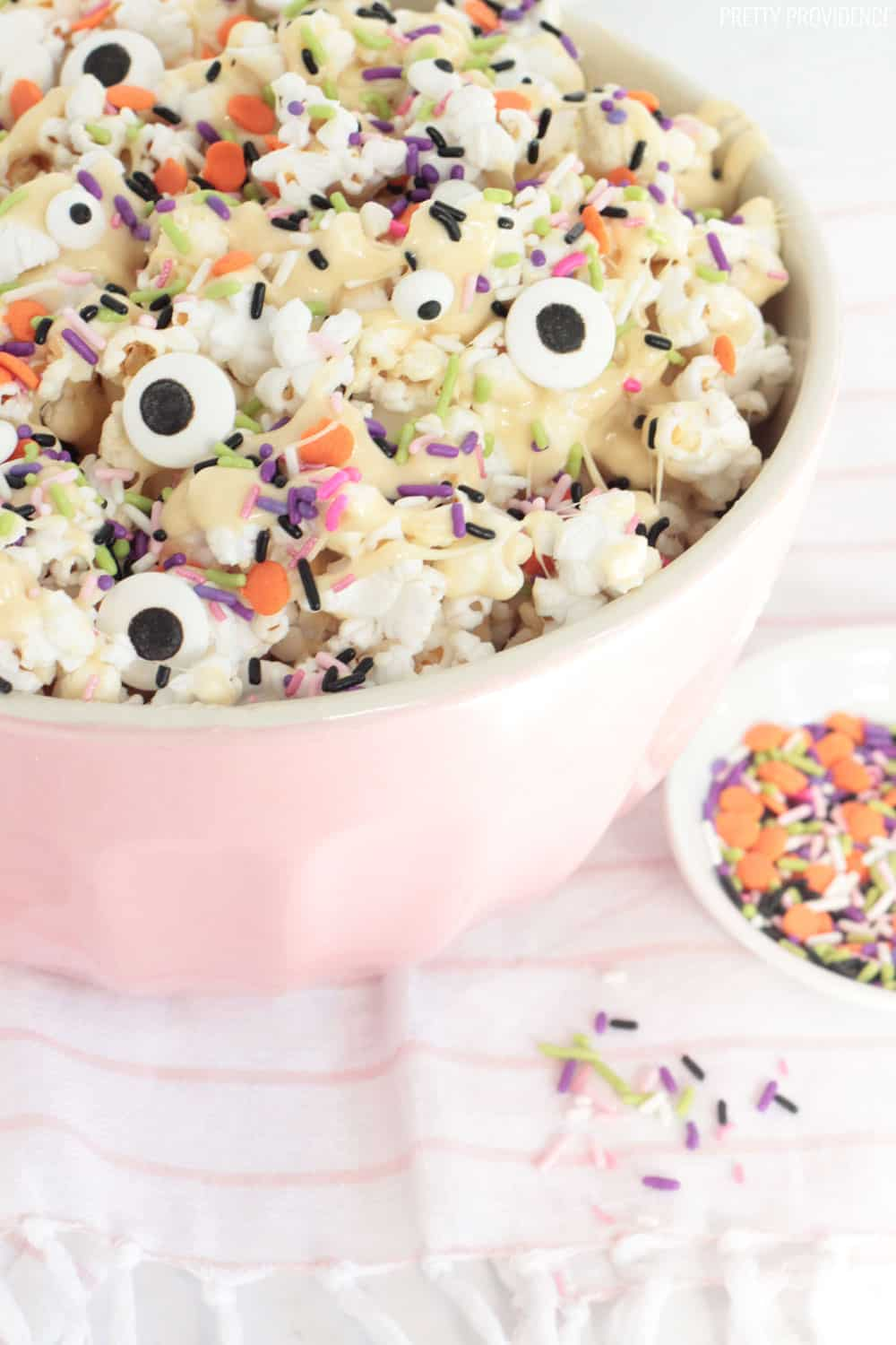 Marshmallow Popcorn in a pink mixing bowl, with Halloween sprinkles and candy eyeballs throughout. Spooky Monster Marshmallow Popcorn!